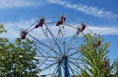 foto of carnival ride  - A ferris wheel carnival ride behind trees and against a blue sky in West Hartford Connecticut - JPG