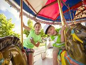 pic of carnival ride  - Cute kids having fun riding on a colorful carnival carousel - JPG