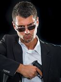 picture of handgun  - Portrait of a man in suit with handgun - JPG