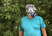foto of gas mask  - An adult man wearing a gas mask against a wooded background - JPG