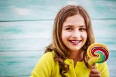 stock photo of lollipops  - Cheerful young girl with a lollipop - JPG