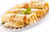 foto of crepes  - Crepes with bananas and cream on white background  - JPG