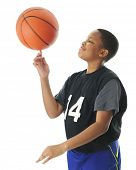 stock photo of preteen  - A preteen boy happily spinning his basketball on his index finger - JPG