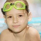 stock photo of goggles  - Little girl in swimming pool with green goggles - JPG