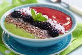 stock photo of blackberries  - Breakfast bowl with green and blackberry smoothie - JPG
