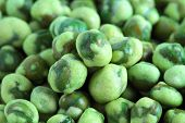 stock photo of green pea  - Close up of a pile of coated green peas - JPG