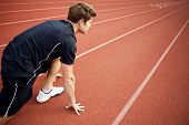 Man ready to start running on a track