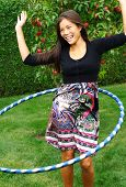 Hula hoop. Beautiful young woman doing hula hoop outdoors in the fall.