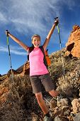 Happy woman hiker holding her arms in the air in a feeling of success having reached the summit. Fro