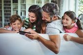 Parents sitting on sofa with their children and using mobile phone in living room at home poster