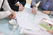 picture of real-estate-team  - group of architect business team people on meeting looking model and desing of new real estate house - JPG
