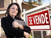 Orgulhoso, atraente hispânico agente feminina na frente do espanhol Se Vende imóveis signo e casa.