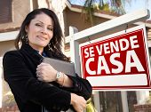 Orgulhoso, atraente agente feminino latino-americano na frente do espanhol Se sinal de imóveis Vende Casa e casa