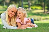 stock photo of family love  - Mother with her daughter lying down in the park - JPG