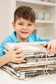 Jornais de reciclagem do menino em casa