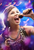 image of young girls  - Portrait of a glamorous girl with mike singing song - JPG