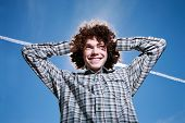 Portrait of a happy young man with curly hair outdoors.