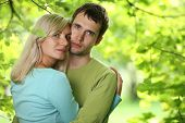 Closeup portrait of young couple in love outdoors, hugging over green foliage background. Shallow DO