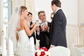 Wedding party bride, groom and bride father clinking glasses with sparkling wine