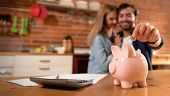 Happy Couple Inserting Coin In Piggybank poster