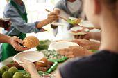 Volunteers Serving Food For Poor People Indoors poster