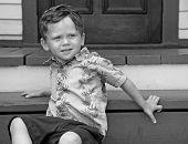 Jonge jongen op trappen van oud huis