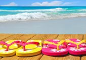 Colorful flip flop sandals on boardwalk with ocean in distance