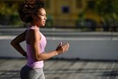 Black Woman, Afro Hairstyle, Running Outdoors In Urban Road. Young Female Exercising In Sport Clothe poster