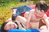 Young brother and sister outdoors in waterplay, laughing and having fun