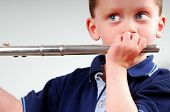 Cute young boy holding flute, pretending to play