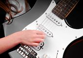 Girl playing electric guitar with hand on strings
