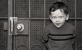 Cute boy standing up against very old screen door