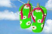 Pretty green and pink flip flop sandals on clothes line under pretty sky
