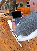 stock photo of screen-porch  - Man relaxing in rocker working on laptop computer on outside deck - JPG