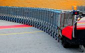Shopping carts being collected by moving cart pusher