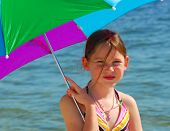 Freckle faced girl under umbrella at beach