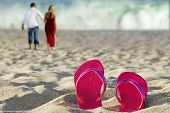 Pink flipflops in sand with couple and oceanin distance
