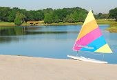 pretty sailboat on beach next to still lake