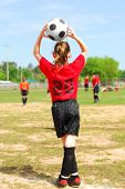 Young soccer player throwing in ball to team on field