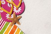 Flip flops on pretty beach towel by sand and starfish