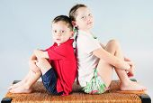 Young boy and girl sitting back to back