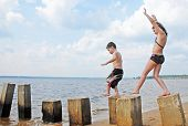 Young kids having fun on pilings at seashore