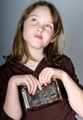 Young girl holding wallet thinking about purchase