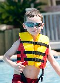 stock photo of floaties  - Young boy in pool wearing safety flotation - JPG
