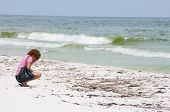 PENSACOLA BEACH - JUNE 23:  An unidentifed beachgoer crouches next to oil covered sand on June 23, 2