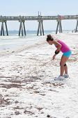 PENSACOLA BEACH - JUNE 23: An unidentifed beach goer looks at oil patches on June 23, 2010 in Pensac