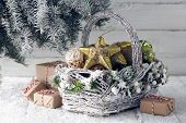Wicker Basket With Christmas Gift Boxes, Toys And Holiday Decorations Under Snowy Fir Tree poster