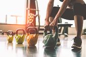 Close Up Of Woman Lifting Kettlebell Like Dumbbells In Fitness Sport Club Gym Training Center With S poster