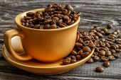 A Coffee Cup With Coffee Beans On An Old Wooden Table. Fried Coffee Beans On A Wooden Background. Vi poster