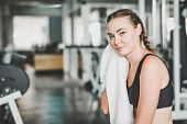 Young Caucasian Woman Wiped Off Her Sweat And Rest In Gym After Workout poster